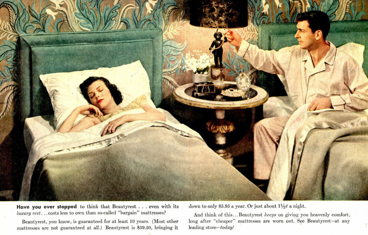 A lady sleeping in bed and a gentlemen turning of the light.