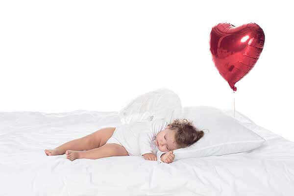baby sleeping in a bed - heart balloon